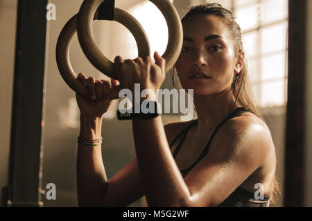 Determined woman exercising with gymnastic rings in gym. Sportswoman standing at  gym holding dip rings. - Stock Photo