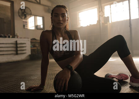 Young woman sitting on gym floor with medicine ball after exercise session. Female taking a break from workout. - Stock Photo