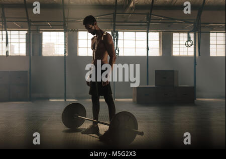 Man exercising with barbell at gym. Man standing with heavy weights barbell on gym floor. - Stock Photo