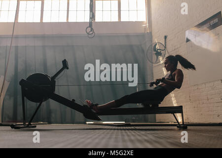 Woman doing cardio workout on rowing machine in the gym. Female exercising in fitness club. - Stock Photo