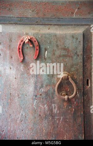 Horseshoe hanging on a rusty door - Stock Photo