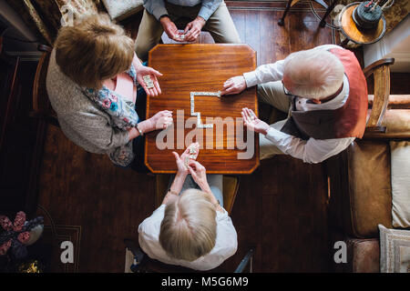 Aerial shot of four senior adults playing dominoes on a table in the nursing home. - Stock Photo