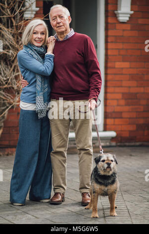 Happy senior couple are posing for the camera outside of their house, with their pet dog on a leash. - Stock Photo
