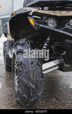 Black ATV quadbike isolated on city pavement, close up - Stock Photo