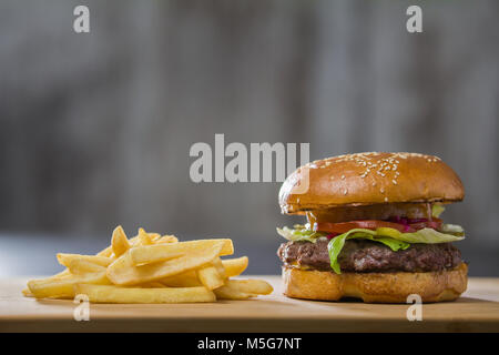 A fresh tasty burger with potatoes on the table - Stock Photo