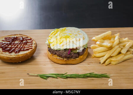 Uncovered tasty burger on the table - Stock Photo