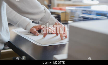 Worker works at polygraph machine, printing industry