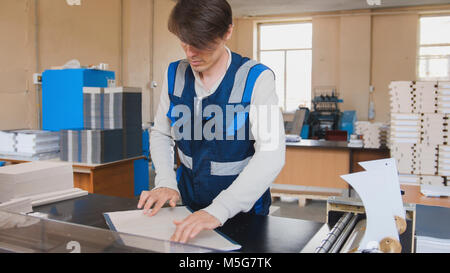 Printing process - worker inserts paper sheets