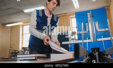 Worker inserts sheets of paper to printing machine, polygraph industry