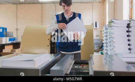 Man worker near printing machine, polygraph industry