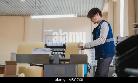 Worker and printing machine, polygraph industry - close up - Stock Photo