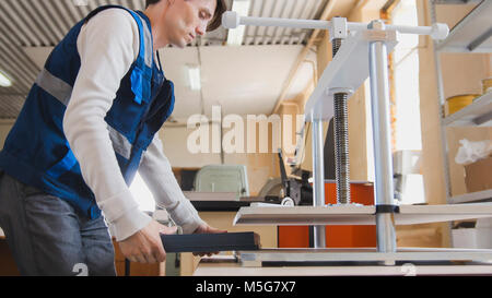 Worker in printing house is engaged in printing