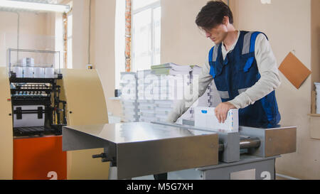 Printing process - worker inserts paper sheets in industrial press