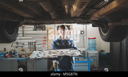 Mechanic in automobile garage repairing workshop - under lifted car - Stock Photo