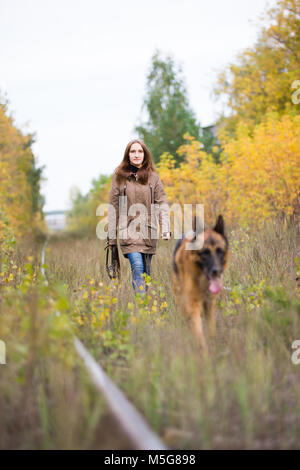 Attractive young woman walking with her dog German shepherd at autumn forest, near rail way - the girl is in focus - Stock Photo