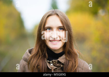 Portrait of young cute woman in fall autumn park. Beautiful caucasian girl walking in forest, close up - Stock Photo