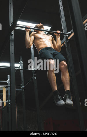 Muscular man practicing pull up on a pull up bar - Stock Photo