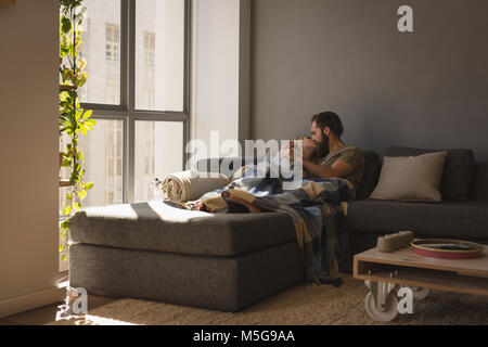 Couple kissing each other in living room - Stock Photo