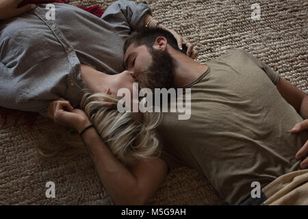 Couple kissing each other while lying in living room - Stock Photo