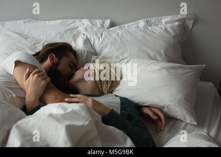 Couple kissing each other in bedroom - Stock Photo