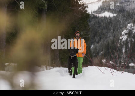 Man walking with his dog on a snowy landscape - Stock Photo