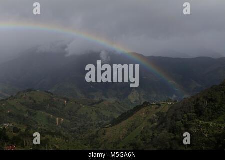 Rainbow over hills farmland Costa Rica - Stock Photo