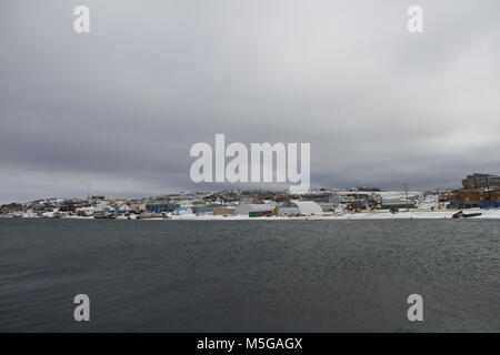 View of Cape Dorset (Kinngait) Nunavut, a northern Inuit community in arctic Canada with the ocean in the foreground - Stock Photo