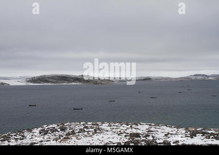 View of Cape Dorset (Kinngait) Nunavut with a view of the ocean and boats, a northern Inuit community in arctic - Stock Photo