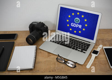 Composite image of laptop, wristwatch, notepad, camera and mobile phone on wooden table - Stock Photo