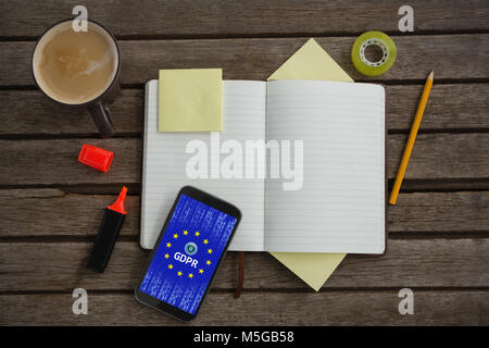 Composite image of organizer, coffee, mobile phone and stationery on wooden plank - Stock Photo