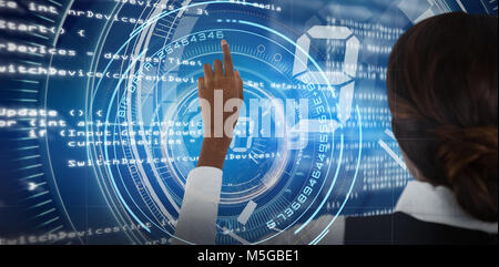 Composite image of rear view of businesswoman touching invisible screen - Stock Photo