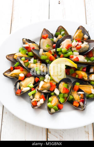 Steamed mussels with peppers and onion on white wooden table - Stock Photo