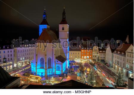 Nighshot of illuminated church at Neupfarrplatz Christmas Market in Bavaria Germany - Stock Photo
