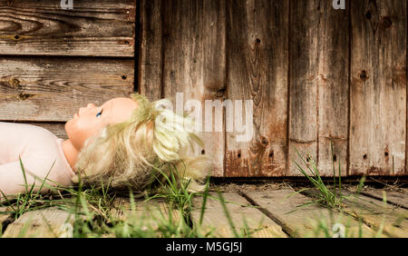 Old neglected doll in front of derelict building. - Stock Photo