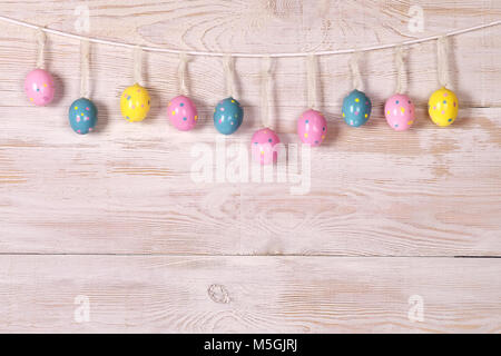 colorful Easter eggs on a rope. wooden wall. vivid colors of Easter eggs. - Stock Photo