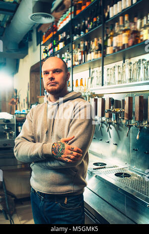 Barman in a pub near beer taps - Stock Photo
