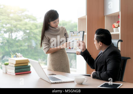 Happy asian businesswoman presenting pile chart to manager in office. Business presentation and meeting concept.