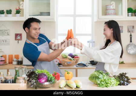 Fun Asian couple mock fighting with carrots as Asian couple cook healthy meal together using fresh vegetables and - Stock Photo