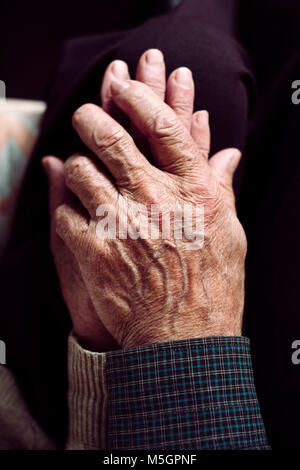 high angle view of an old caucasian man and an old caucasian woman sitting in a couch holding hands with affection - Stock Photo