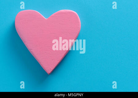 closeup of a pink three-dimensional heart on a blue background, with a blank space on the right - Stock Photo