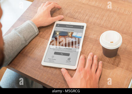 Real estate agency web site on property agent laptop. Coffee beside. - Stock Photo