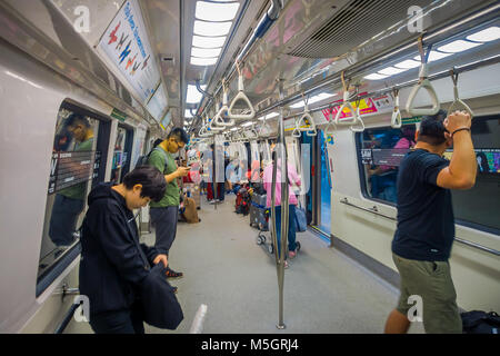 SINGAPORE CITY, SINGAPORE - NOV 13, 2013: Indoor view of rail commuters ride a crowded Mass Rapid Transit MRT train - Stock Photo