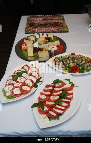 Food tray with delicious and different cheese with delicious salami, pieces of sliced ham and tomatoes - Stock Photo