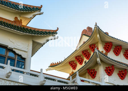 View of the chinese-inspired architecture of the Huatian Chinagora hotel complex with curved roof corners and traditional glazed roof tiles. Stock Photo
