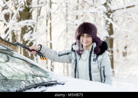 The girl is brushing the windshield of the car from the snow. Winter, day. - Stock Photo