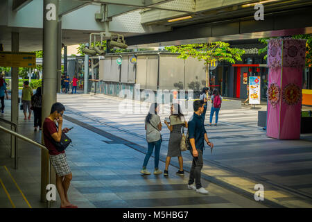 SINGAPORE, SINGAPORE - JANUARY 30, 2018: Outdoor view of unidentified people walking in the sidewalks close to at - Stock Photo