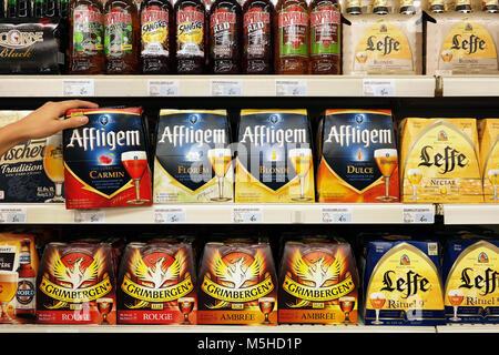 Assortment of different brands cardboard 6-packs beer bottles in a Super U supermarket. - Stock Photo