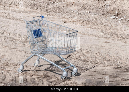 shopping cart standing outside on a terrain in the sand - Stock Photo
