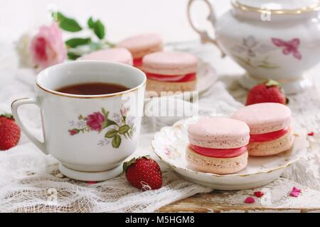 Homemade Pink Macaroons or Macarons with a cup of coffee / Valentines day dessert for two on rustic wooden frame - Stock Photo