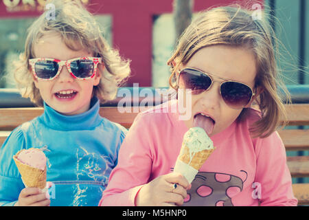 Two little girls (sisters) eating ice cream. - Stock Photo